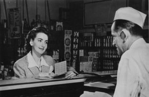 A retro photograph of a customer at the counter in a pharmacy