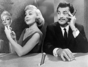 A woman turns away from an exasperated man with a mustache and cigar and looks at him through a hand held mirror