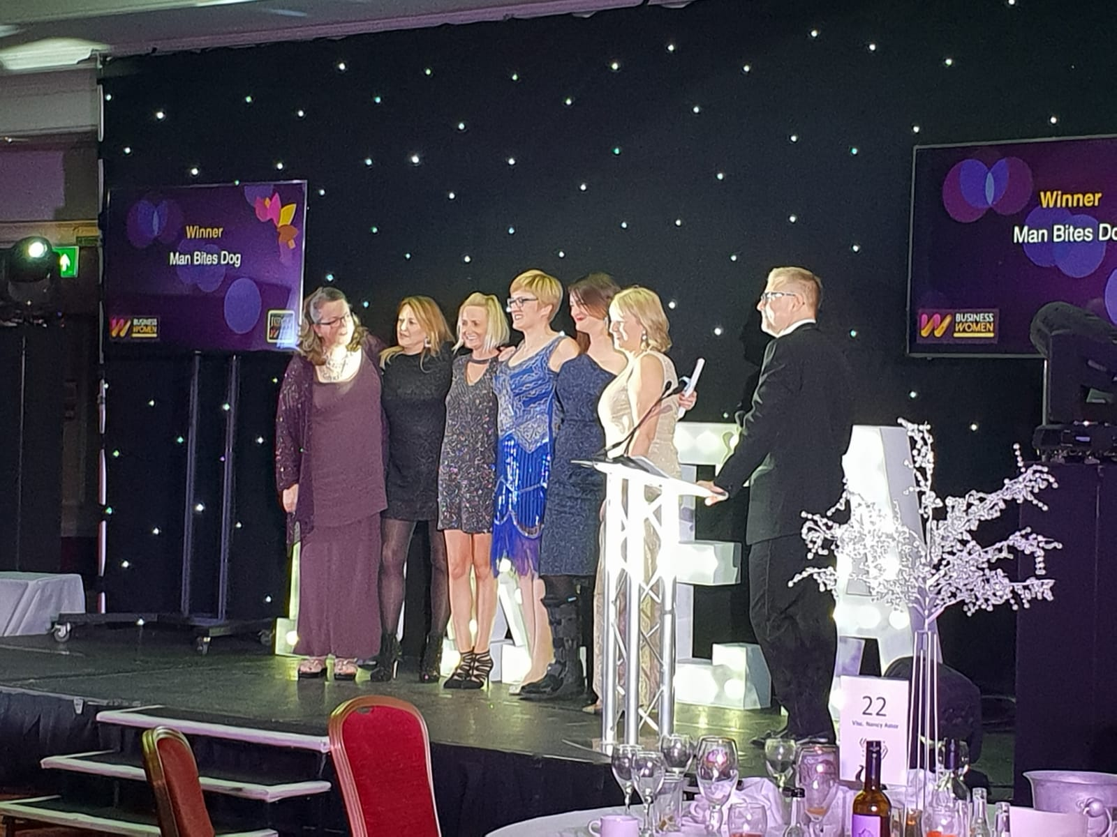 Man Bites Dog on stage after being voted Business of the Year at the Business Women Excellence Awards 2018 for Sussex.